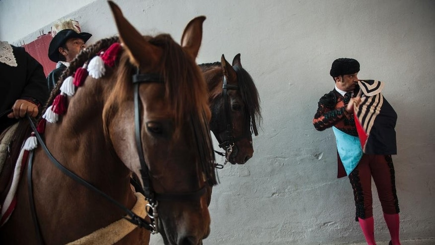 An assistant to a Spanish mounted bullfighter waits on the sidelines during a horseback bullfight at San Fermin Fiestas, in Pamplona, northern Spain, Monday, July 6, 2015. Revelers from around the world kick off the festival with a messy party in the Pamplona town square, one day before the first of eight days of the running of the bulls. (AP Photo/Alvaro Barrientos)