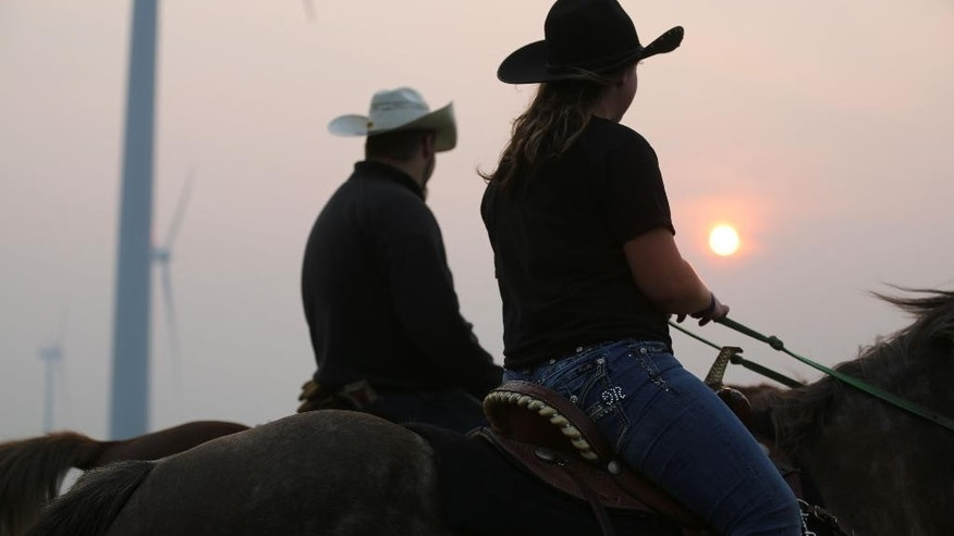 Carley Wentworth, right, of Bolan, and Bo Miller, of Kensett, ride horses in rural Worth County on Monday, July 6, 2015.  A large plume of smoke from wildfires in Canada has drifted into North Iowa causing a dense haze across the area.  Air quality advisories have been issued.  (Arian Schuessler/Globe-Gazette via AP)