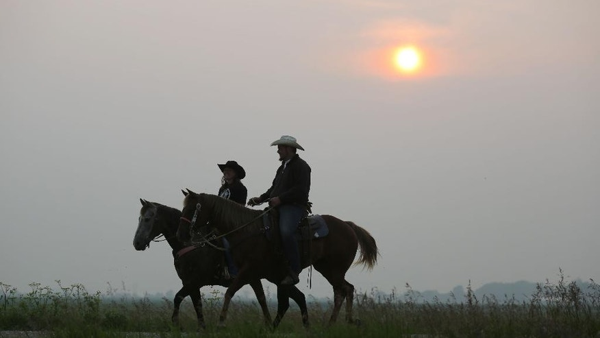 Carley Wentworth, left, of Bolan, and Bo Miller, of Kensett, ride horses in rural Worth County on Monday, July 6, 2015.  A large plume of smoke from wildfires in Canada has drifted into North Iowa causing a dense haze across the area.  Air quality advisories have been issued.  (Arian Schuessler/Globe-Gazette via AP)