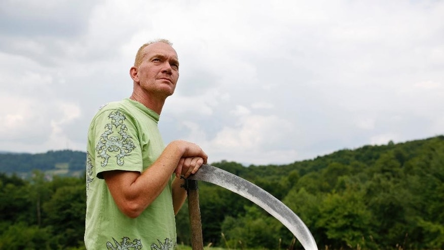 In this photo taken on Monday, June 29, 2015, Rob Zomer Dutch a UN veteran takes a break from cutting grass with scythe in his garden, near Srebrenica, 150 kms northeast of Sarajevo, Bosnia. Zomer was a member of the Dutch battalion of United Nations peacekeepers who failed to halt the slaughter by Bosnian Serb forces of some 8,000 Muslim men and boys in Srebrenica. (AP Photo/Amel Emric)