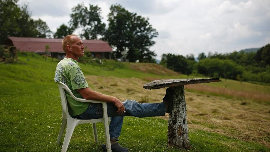 In this photo taken on Monday, June 29, 2015, Rob Zomer a Dutch UN veteran relaxing after work in his garden, near Srebrenica, 150 kms northeast of Sarajevo, Bosnia.  (AP Photo/Amel Emric)