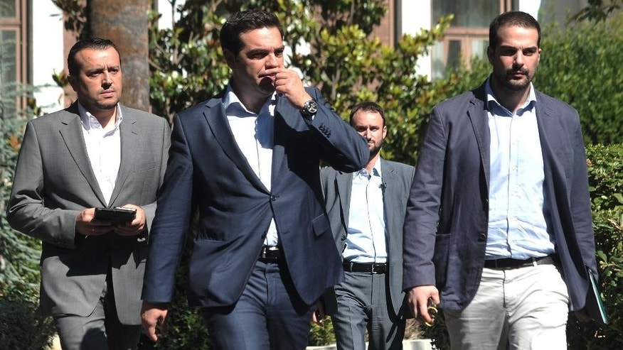 Greece's Prime Minister Alexis Tsipras, center, leaves after a meeting with Greek political party leaders at the Presidential Palace as Minister of State Nikos Pappas, left, and Government spokesman Gabriel Sakellaridis, right, follow him in Athens, Monday, July 6, 2015. Greece and its membership in Europe's joint currency faced an uncertain future Monday, with the country under pressure to reach a bailout deal with creditors as soon as possible after Greeks resoundingly rejected the notion of more austerity in exchange for aid. (AP Photo/Angelos Christofilopoulos)