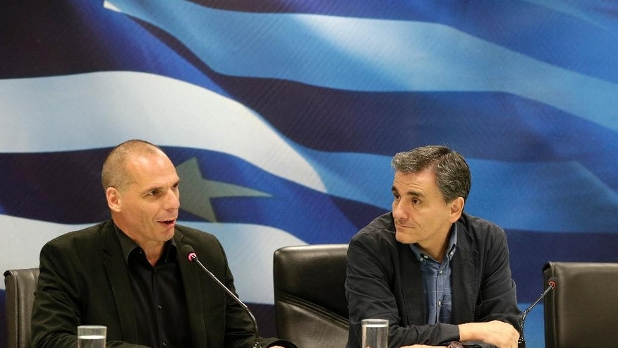 Outgoing Greek Finance Minister Yanis Varoufakis, left, speaks as the new Finance Minister Euclid Tsakalotos listens to him during a hand over ceremony in Athens, Monday, July 6, 2015. Following Sunday's referendum the Greece and its membership in Europe's joint currency faced an uncertain future Monday, with the country under pressure to restart bailout talks with creditors as soon as possible after Greeks resoundingly rejected the notion of more austerity in exchange for aid. (AP Photo/Petr David Josek)