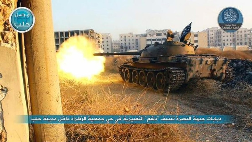 In this image posted on the Twitter page of Syria's al-Qaida-linked Nusra Front on early Tuesday, July 7, 2015, a tank from the Nusra Front fires during their clashes against the Syrian government forces at the western Zahra neighborhood in Aleppo city, Syria. Intense clashes broke out in the northern Syrian city of Aleppo after militants attacked the government-held neighborhood, capturing several buildings, activists said. (Al-Nusra Front Twitter page via AP)