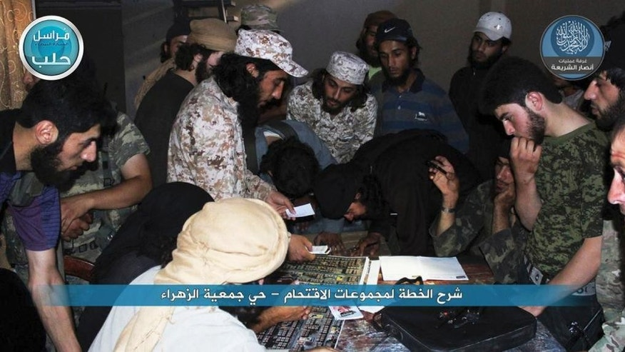 In this image posted on the Twitter page of Syria's al-Qaida-linked Nusra Front on early Tuesday July 7, 2015, one of the leaders of the Nusra Front, center left, explains to his fighters an attack plan against the Syrian government forces at the western Zahra neighborhood in Aleppo city, Syria. Intense clashes broke out in the northern Syrian city of Aleppo after militants attacked the government-held neighborhood, capturing several buildings, activists said. (Al-Nusra Front via AP)