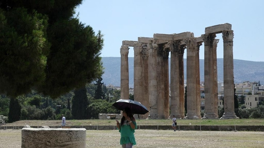 A tourist holds an umbrella to protect from the sun as she visits the Temple of Zeus in Athens, Tuesday, July 7, 2015. This is Greek tourism - July 2015 style - as the peak summer season in one of the world's most popular destinations is glitched by a financial crisis of frightening proportions. The World Travel and Tourism Council said tourism's direct contribution to the Greek economy was more than 29 billion euros in 2014, accounting for just over 17 percent of the country's GDP. (AP Photo/Spyros Tsakiris)