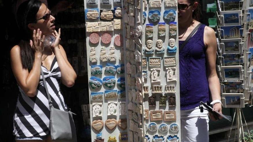 Two women buy souvenirs at the Plaka tourist district of Athens, Tuesday, July 7, 2015. This is Greek tourism - July 2015 style - as the peak summer season in one of the world's most popular destinations is glitched by a financial crisis of frightening proportions. The World Travel and Tourism Council said tourism's direct contribution to the Greek economy was more than 29 billion euros in 2014, accounting for just over 17 percent of the country's GDP. (AP Photo/Spyros Tsakiris)