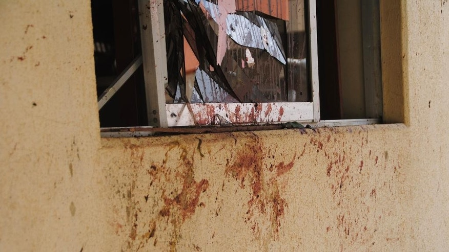 A blood splattered wall and broken window lay testament after a bomb blast in Zaria, Nigeria, Tuesday, July 7, 2015. A bomb blast in Nigeria's northern university town of Zaria killed 25 people Tuesday including a 2-year-old toddler, the Kaduna state governor reported, Tuesday, the latest in a string of deadly bombing and shooting attacks attributed to the Boko Haram Islamic extremist group.(AP Photo)