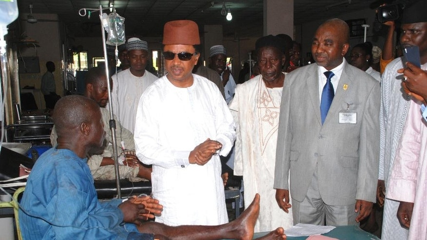 Nigerian senator Shehu Sani from Kaduna state, second left, talk to an injured man after a bomb blast as he and others receive medical treatment at a hospital in  Zaria, Nigeria, Tuesday, July 7, 2015. A bomb blast in Nigeria's northern university town of Zaria killed 25 people Tuesday including a 2-year-old toddler, the Kaduna state governor reported, Tuesday, the latest in a string of deadly bombing and shooting attacks attributed to the Boko Haram Islamic extremist group.(AP Photo)