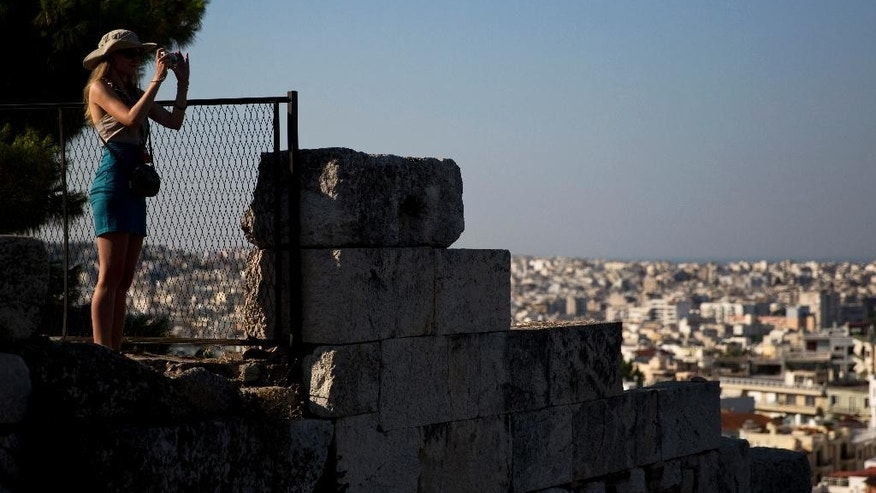 A tourist takes a picture during her visit to the ancient Acropolis hill,  with the city of Athens in the background, on Tuesday, July 7, 2015. Greek Prime Minister Alexis Tsipras was heading Tuesday to Brussels for an emergency meeting of eurozone leaders, where he will try to use a resounding referendum victory to eke out concessions from European creditors over a bailout for the crisis-ridden country. (AP Photo/Petros Giannakouris)