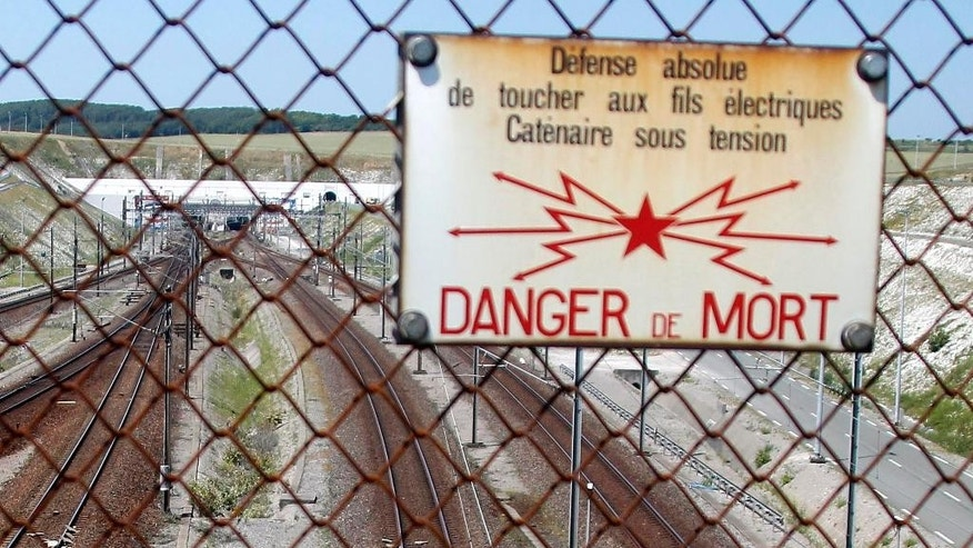 FILE - In this June 30 2015 file photo, a poster warns about the risk of death on rail tracks ahead of the Channel tunnel, during a workers ferry workers protest in Calais, northern France. French authorities say a migrant has died in the Channel Tunnel between France and England. The reported death Tuesday came shortly after Eurotunnel reported a group of migrants was found in the tunnel leading from Calais in northern France.(AP Photo/Michel Spingler, File)