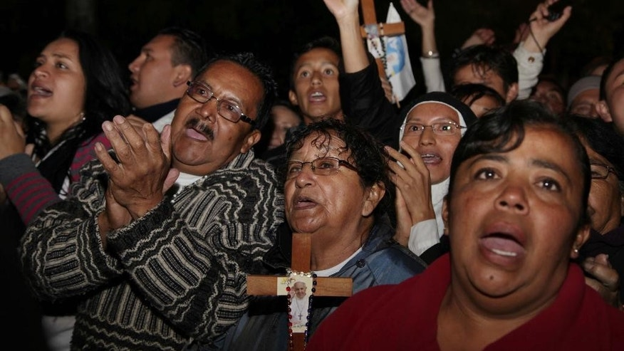 People sing at Independence square, while they wait for the Pope's arrival to the government palace in Quito, Ecuador, Monday, July 6, 2015. Pope Francis is making his first visit to his Spanish-speaking neighborhood. He travels to three South American nations, Ecuador, Bolivia and Paraguay. (AP Photo/Ana Buitron)