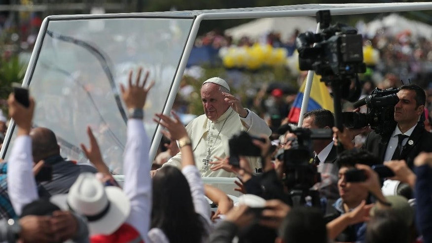 Pope Francis waves as he arrives to celebrate Mass at Bicentennial Park in Quito, Ecuador, Tuesday, July 7, 2015. Pope Francis is beginning his second full day of his South American tour. (AP Photo/Fernando Llano)