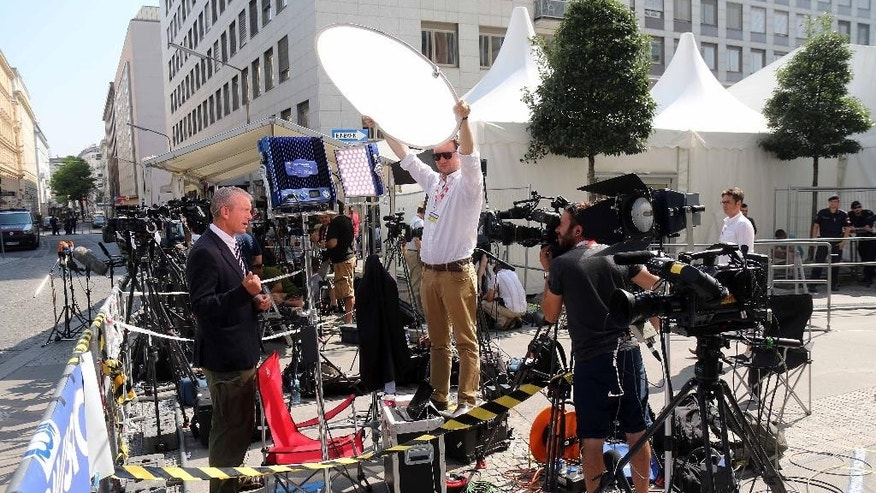 A journalist talks into a TV camera in front of Palais Coburg where closed-door nuclear talks with Iran take place in Vienna, Austria, Tuesday, July 7, 2015. The talks are in danger of busting through their second deadline in a week, raising questions about whether world powers can cut off all Iranian pathways to a bomb through diplomacy — and testing the resolve of U.S. negotiators to walk away from negotiations. (AP Photo/Ronald Zak)
