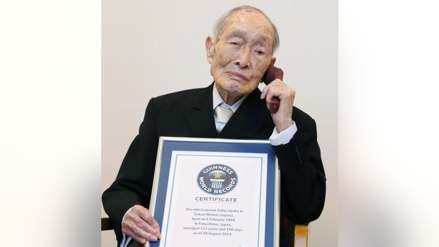 FILE - In this Aug. 20, 2014 file photo, Sakari Momoi, a Japanese retired educator, poses for a photo after receiving a certificate from Guinness World Records as Momoi was recognized as the world's oldest living man, in Tokyo. An official at Saitama City said Tuesday, July 7, 2015 that Sakari Momoi died on Sunday at a nursing home in Tokyo. He was 112. (Kyodo News via AP, File) JAPAN OUT, CREDIT MANDATORY