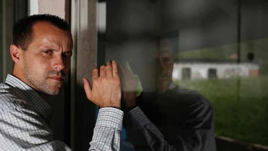 In this photo taken, Saturday, June 27, 2015, Srebrenica massacre survivor Nedzad Avdic , 37, looks through a window inside the elementary school where he was brought by Serb soldiers in the village of Petkovci near Zvornik, 200 kilometers (124 miles) north of Sarajevo, to be killed. He was 17 when he joined the other men who tried to flee through the woods.  His group was hunted down by Serb soldiers and brought to the school for execution. The warehouse in the window's relection  was one of the execution sites. ( AP Photo/Amel Emric)