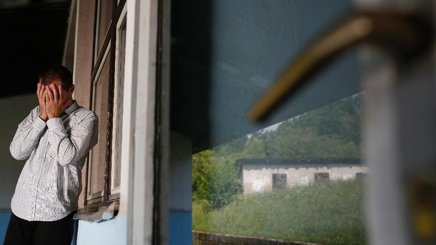 In this photo taken on Saturday, June 27, 2015, Srebrenica massacre survivor Nedzad Avdic, 37, cover his face as he tries to collect his thoughts during a visit to the elementary school in Petkovci, 200 kilometers (124 miles) north of Sarajevo, where Serb soldiers had brought him for execution 20 years ago.  (AP Photo/Amel Emric)
