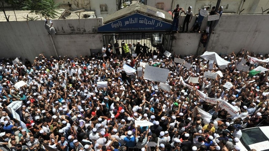 Hundreds of demonstrators of the Berber community stage a protest in front of a walled area where Algier's newspapers are headquartered in support of Berbers in the southern Ghardaia region where at least 22 people have died in ethnic unrest, in Algiers, Algeria, Wednesday, July 8, 2015. Authorities say ethnic clashes have left at least 22 people dead around Algeria's southern oasis city of Ghardaia, more than 600 kilometers (375 miles) south of Algiers, prompting the president to call an urgent security meeting. The Berbers and the Arabs in Ghardaia had for centuries lived together in harmony, but tensions started in late 2013 when a Berber shrine was vandalized. (AP Photo/Sidali Djarboub)