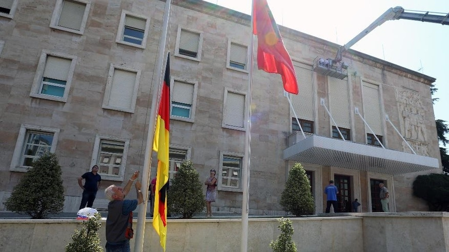 Flags are raised at Albania's government building to welcome German Chancellor Angela Merkel in Tirana, Wednesday, July 8, 2015. Merkel is on a Balkan trip to Albania, Serbia and Bosnia, which are all looking forward to becoming European Union members one day. (AP Photo/Hektor Pustina)