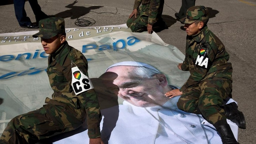 Air Force soldiers sit on top of a banner with the portrait of Pope Francis before placing it in front of the headquarters of the Air Force in La Paz, Bolivia, Tuesday, July 7, 2015. The Pontiff is visiting Ecuador, Bolivia and Paraguay on the occasion of his Apostolic trip from July 5 to July 12. (AP Photo/Rodrigo Abd)