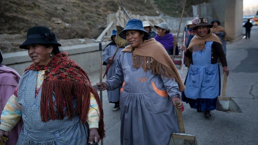 Women hired to clean the roads and gardens before the visit of  Pope Francis to El Alto, walk back to the municipality to return their tools, at the end of the work day in El Alto, Bolivia, Tuesday, July 7, 2015. The pope will arrive to Bolivia on Wednesday during his South American tour. (AP Photo/Rodrigo Abd)