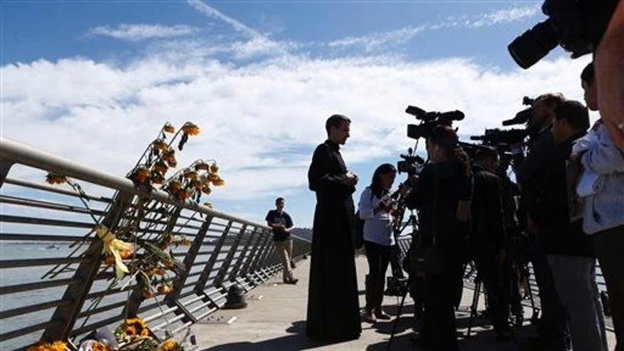 Father Cameron Faller, of Restorative Justice Ministry, answers questions before a vigil for Kathryn Steinle, Monday, July 6, 2015, on Pier 14 in San Francisco.