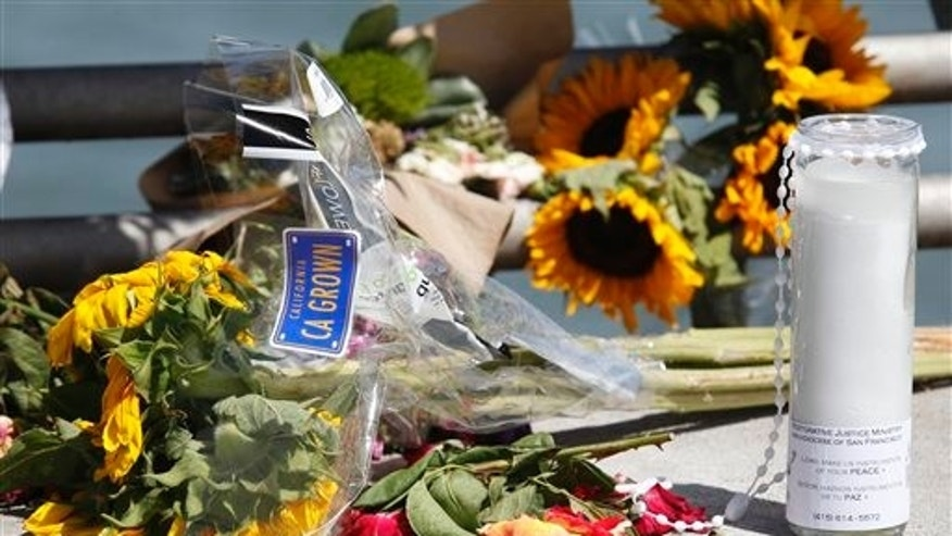 Flowers and a candle lay on the ground following a vigil for Kathryn Steinle, Monday, July 6, 2015, on Pier 14 in San Francisco.