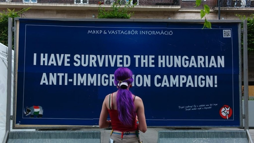 A young woman looks at a satirical billboard in downtown Budapest, Hungary on Wednesday July 8, 2015. Hundreds of crowd-funded satirical billboards are being set up across the country to counter the government's anti-immigration campaign. The humorous Two-Tailed Dog Party, says over 7,000 people gave 33.3 million forints ($115,000, euro105,000 ) for the billboard campaign against the Hungarian government's own anti immigration campaign.  (AP Photo/Bela Szandelszky)