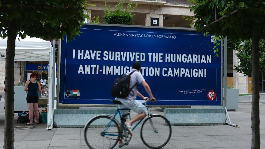A man looks at a satirical billboard in downtown Budapest, Hungary on Wednesday July 8, 2015. Hundreds of crowd-funded satirical billboards are being set up across the country to counter the government's anti-immigration campaign. The humorous Two-Tailed Dog Party, says over 7,000 people gave 33.3 million forints ($115,000, euro105,000) for the billboard campaign against the Hungarian government's own anti immigration campaign. (AP Photo/Bela Szandelszky)