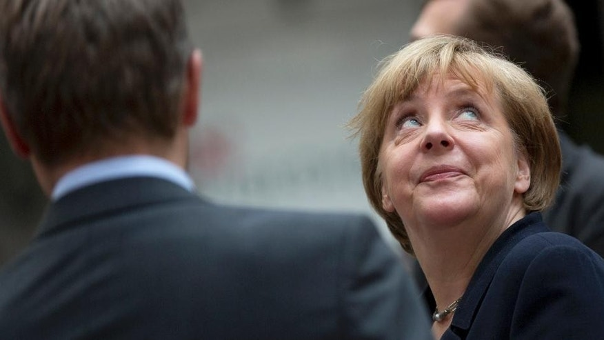 German Chancellor Angela Merkel looks up as she arrives for an emergency summit of eurozone heads of state or government at the EU Council building in Brussels on Tuesday, July 7, 2015. Greek Prime Minister Alexis Tsipras was heading Tuesday to Brussels for an emergency meeting of eurozone leaders, where he will try to use a resounding referendum victory to eke out concessions from European creditors over a bailout for the crisis-ridden country. (AP Photo/Virginia Mayo)