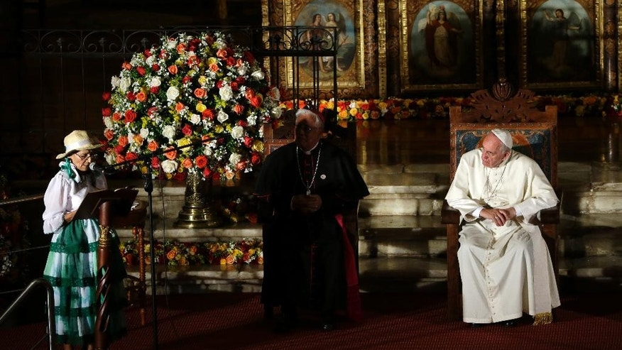 IDENTIFIES WOMAN ON THE LEFT - Pope Francis listens to a speech by Imelda Caicedo, left, a delegate of the Ecuadorian coastal farmers association, during his visit to the San Francisco Church in Quito, Ecuador, Tuesday, July 7, 2015. Francis is making his first visit as pope to his Spanish-speaking neighborhood. He travels to three South American nations, Ecuador, Bolivia and Paraguay. (AP Photo/Gregorio Borgia)