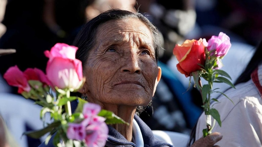 An elderly woman holds a posy of orange and pink flowers as she waits for the arrival of Pope Francis outside the National Shrine of Our Lady of the Presentation of El Quinche, in El Quinche, Ecuador, Wednesday, July 8, 2015. Francis wraps up the first leg of a three-nation South American pilgrimage Wednesday. Next stop on the pope's South American tour is La Paz, Bolivia, where he will be welcomed by President Evo Morales. (AP Photo/Ana Buitron)