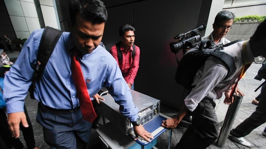 Malaysian plainclothes police carry a computer from the 1MDB (1 Malaysia Development Berhad) office after a raid in Kuala Lumpur, Malaysia, Wednesday, July 8, 2015. Malaysian authorities have frozen six bank accounts as part of an investigation into allegations that hundreds of millions of dollars were transferred from a state investment fund to the personal accounts of Prime Minister Najib Razak. (AP Photo/Joshua Paul)