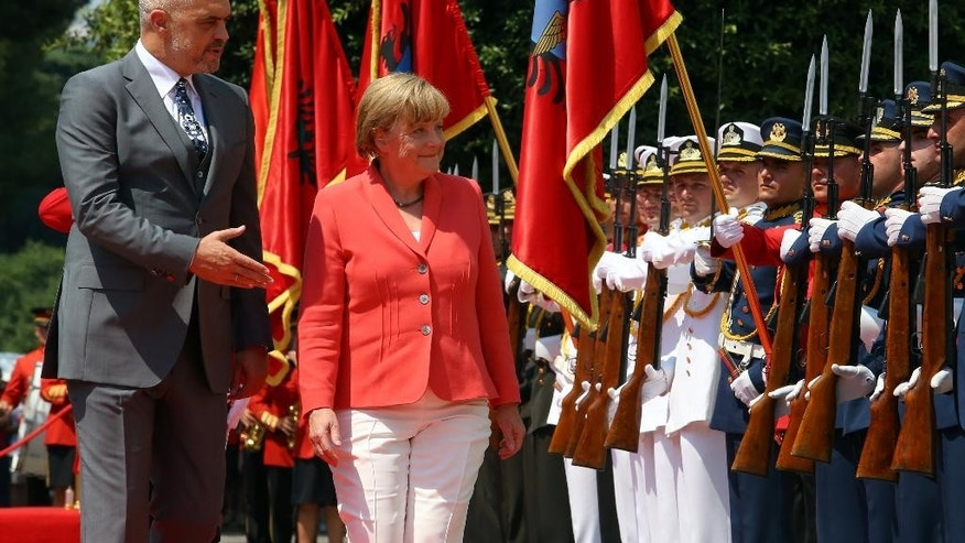 Visiting German Chancellor Angela Merkel and host Albanian counterpart Edi Rama, left, walk the Guard of Honor in the first stop of her Balkan tour in Tirana Wednesday, July 8, 2015. Merkel has urged Albania to fulfill five categories presented by the European Union in December regarding its public administration and justice system ahead of launching full membership talks. Last year Albania was granted candidate status. (AP Photo/Hektor Pustina)