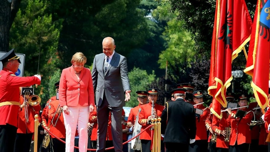 Visiting German Chancellor Angela Merkel, left, and host Albanian counterpart Edi Rama, leave the dais to walk the Guard of Honor in the first stop of her Balkan tour in Tirana Wednesday, July 8, 2015. Merkel has urged Albania to fulfill five categories presented by the European Union in December regarding its public administration and justice system ahead of launching full membership talks. Last year Albania was granted candidate status. (AP Photo/Hektor Pustina)