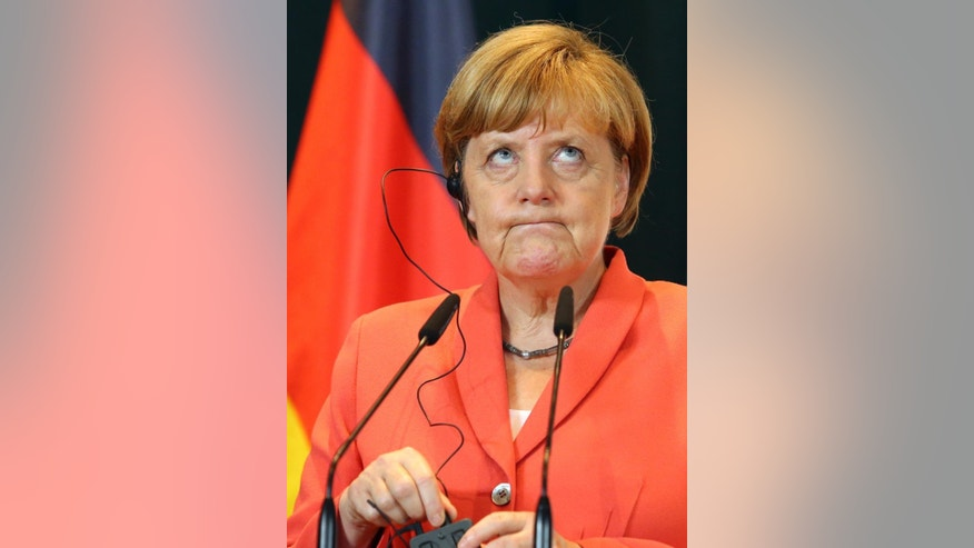 Visiting German Chancellor Angela Merkel adjusts her headphone feed during a news conference after meeting with Albanian Prime Minister Edi Rama, on the first stop of the Balkan tour in Tirana Wednesday, July 8, 2015. Merkel has urged Albania fulfill five categories presented by the European Union in December regarding its public administration and justice system ahead of launching full membership talks. Last year Albania was granted the candidate status. (AP Photo/Hektor Pustina)