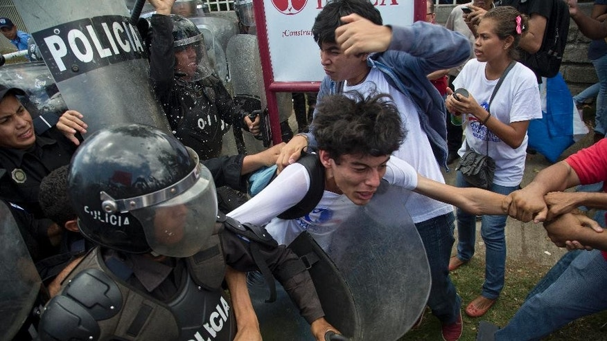 An anti-government protester is pulled between police and fellow protesters during a demonstration demanding fair elections, near the Supreme Electoral Council in Managua, Nicaragua, Wednesday, July 8, 2015. Demonstrators are demanding clean elections for Nicaragua's 2016 general elections slated for November. (AP Photo/Esteban Felix)