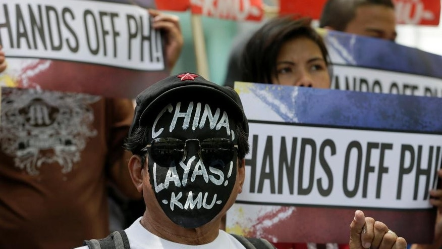 "Protesters display placards during a rally near the Chinese Consulate at the financial district of Makati city, east of Manila, Philippines, Tuesday, July 7, 2015 on the complaint filed by the Philippines against China's claims of the disputed islands in the South China Sea. The rally coincided with the oral arguments scheduled Tuesday before the Arbitral Tribunal in the Permanent Court of Arbitration at The Hague in the Netherlands. The disputed islands known as the Spratlys Group of islands is claimed by China, Philippines, Brunei, Malaysia, Taiwan and Vietnam. The message on the mask reads: ""China hands off!"" (AP Photo/Bullit Marquez)"