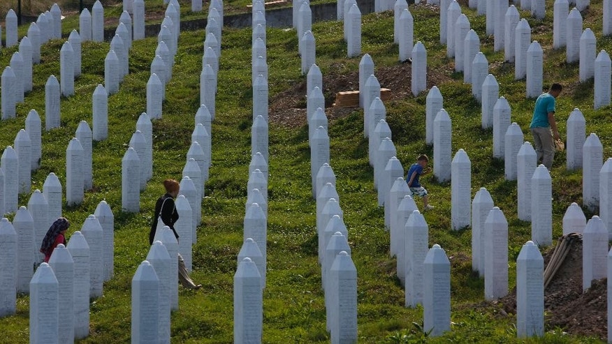 Bosnian people visit graves  at memorial center in Potocari near Srebrenica, 150 kms north east of Sarajevo, Bosnia, on Wednesday, July 8,2015. The memorial center  in Potocari, is a cemetery for the victims of the Srebrenica massacre killed in the summer of 1995 during the worst atrocity on European soil since the Second World War.(AP Photo/Amel Emric)