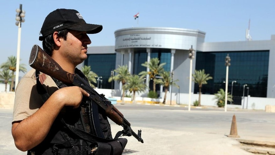 A police officer stands guard in front of the Iraqi Supreme court in Baghdad, Iraq, Wednesday, July 8, 2015. An Iraqi court has issued death sentences to 24 militants for their role in killing hundreds of soldiers last year. The slain soldiers were captured by the Islamic State group when they overran Saddam Hussein's hometown of Tikrit in summer 2014. At the time, the soldiers were trying to flee from a nearby army base. (AP Photo/ Karim Kadim)