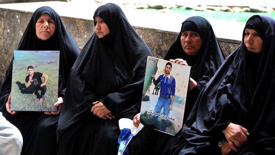 Mothers hold up posters of their sons,  Iraqi soldiers who were killed, at a courtroom in Baghdad, Iraq, Wednesday, July 8, 2015. An Iraqi court has issued death sentences to 24 militants for their role in killing hundreds of soldiers last year. The slain soldiers were captured by the Islamic State group when they overran Saddam Hussein's hometown of Tikrit in summer 2014. At the time, the soldiers were trying to flee from a nearby army base. (AP Photo/ Karim Kadim