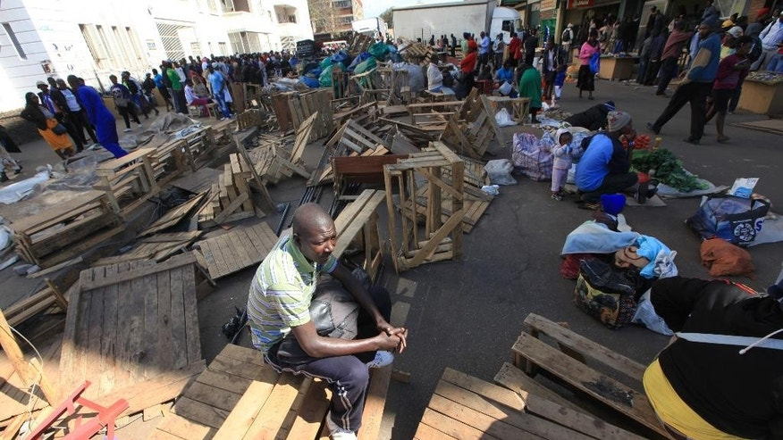 A Zimbabwean vendor ponders his next move after he had his wares removed by police from the streets of Harare, Wednesday, July, 8, 2015. Minor scuffles ensued as police  officers drove out thousands of vendors selling their wares on the sidewalks and pavements of Harare. (AP Photo/Tsvangirayi Mukwazhi)