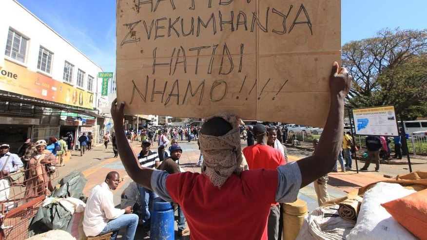 Vendors hold placards written in the local language, shona, saying they will not move after they were removed from the streets of Harare, Wednesday, July, 8, 2015. Minor scuffles ensued as police officers drove out thousands of vendors selling their wares on the sidewalks and pavements of Harare. (AP Photo/Tsvangirayi Mukwazhi)