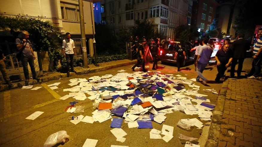 Files and documents of the Thai consulate in Istanbul, litter the street, after protesters entered and threw them out, early Thursday, July 9, 2015. A group of protesters stormed the consulate overnight, smashing windows and breaking in to the offices, where they destroyed pictures and furniture and hurled files out into the yard, to denounce Thailand's decision to deport 109 ethnic Uighur migrants back to China. Turkey has cultural ties to the minority Muslim Uighurs and pro-Uighur groups fear the 109 face persecution by the Chinese government. (AP Photo)
