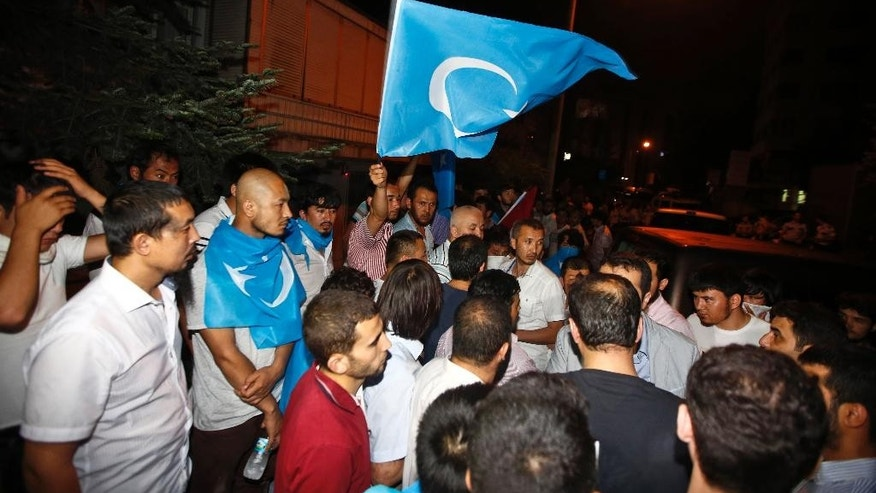 Uighurs living in Turkey and Turkish supporters, some carrying flags of East Turkestan, the term separatist Uighurs and Turks use to refer to the Uighurs homeland in China's Xinjiang region, gather outside the Thai consulate in Istanbul, early Thursday, July 9, 2015. A group of protesters stormed the consulate overnight, smashing windows and breaking in to the offices, where they destroyed pictures and furniture and hurled files out into the yard, to denounce Thailand's decision to deport 109 ethnic Uighur migrants back to China. Turkey has cultural ties to the minority Muslim Uighurs and pro-Uighur groups fear the 109 face persecution by the Chinese government. (AP Photo)