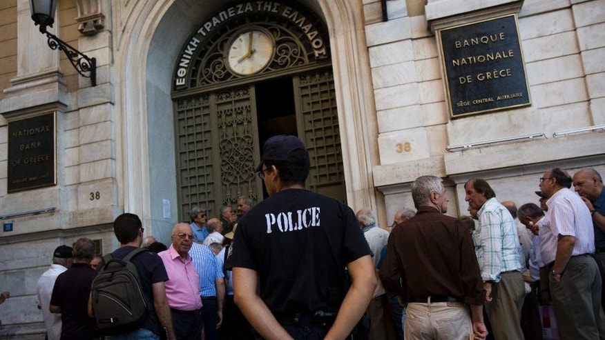 A police officer stands as pensioners wait outside the main gate of the national bank of Greece to withdraw a maximum of 120 euros ($134) in central Athens, Thursday, July 9, 2015. With a deadline just hours away to come up with a detailed economic reform plan, Greece requested a new three-year rescue from its European partners Wednesday as signs grew its economy was sliding toward free-fall without an urgently needed bailout. (AP Photo/Emilio Morenatti)