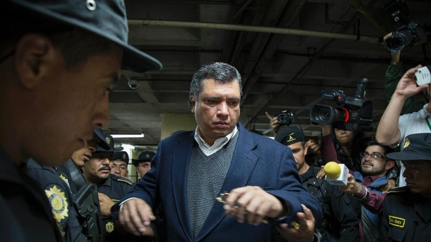 Gustavo Martinez,  son-in-law of Guatemala's President Otto Perez Molina, arrives to court escorted by police in Guatemala City, Thursday, July 9, 2015. Martinez, who had served until April 2015, as the President's private secretary, was arrested based on investigations by the federal prosecutors' office and the U.N. International Commission Against Impunity in Guatemala for alleged influence trafficking. (AP Photo/Luis Soto)