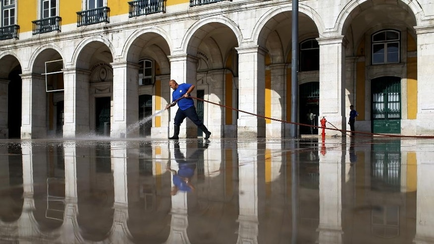 In this photo taken on Wednesday, July 8, 2015, street cleaner Rui Santos works with a hose at the Comercio square, in Lisbon. Santos, who has been working for the local administration for seven years, earns euro 505 ($556) per month, which is the minimum salary in Portugal. Despite the austerity, not all the country's financial statistics are flattering. (AP Photo/Francisco Seco)