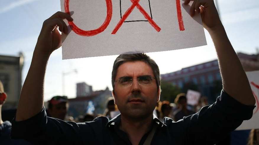 "In this photo taken on Saturday, July 4, 2015, a man holds a banner that reads in Greek: ""No"", referring to the  referendum in Greece on Sunday July 5, during a rally in support of the Greek government, in Lisbon. Eurozone governments taking a tough line on Greece's demand for debt relief fear opening a potentially bigger can of worms in countries like Portugal, which also needed a bailout. A decade of spending more than it earned pushed Portugal close to bankruptcy in 2011. The 78 billion euro bailout loan it got that year was added to its already massive debt pile. (AP Photo/Francisco Seco)"