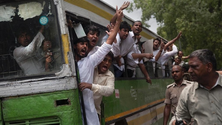"""Activists of India's Congress party's youth wing shout slogans from a bus as they are detained during a protest against Shivraj Singh Chauhan, chief minister of the central Indian state of Madhya Pradesh, in New Delhi, India, Wednesday, July 8, 2015. Protests against Chauhan and his administration has peaked in recent days after several witnesses in a case alleging a massive scheme to manipulate the results of entrance examinations for government jobs and medical colleges in Madhya Pradesh died under mysterious circumstances. The alleged scam has been labeled """"Vyapam"""" by Indian media after the Hindi name of the state's professional examination board since the story first surfaced in 2013. (AP Photo/Tsering Topgyal)"""